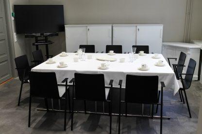 Kokoushuoneen pöytä katettuna kahviastioilla